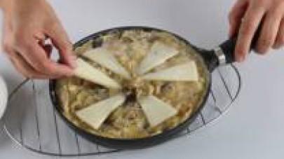 Aggiungete il formaggio tagliato a triangoli su tutta la superficie della frittata e giratela aiutandovi con un piatto piano o un coperchio.