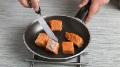 Soffriggete in una padella con un cucchiaio di olio il salmone a dadini senza la pelle.