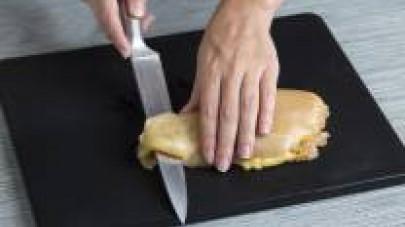 Aprite i petti di pollo a metà e farciteli con una fetta di formaggio, uno strato di prosciutto e le strisce di peperone rosso arrostito.