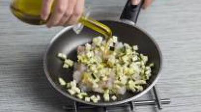Tagliate il porro, lo zucchino e lo scalogno a dadini molto piccoli e fate soffriggere le verdure in una padella con 2 cucchiai d'olio extravergine d'oliva.