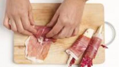 Avvolgete il crudo sugli spicchi di radicchio stringendo un pochino perché non si apra durante la cottura.
