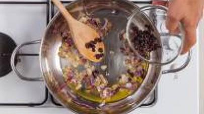 In una pentola preparate il soffritto con la cipolla di Tropea, unite l'uvetta e il cous cous di mais tostato.
