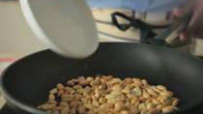 Ponete i centoventicinque grammi di arachidi e i cinquanta grammi di pinoli in una padella e li mettete a scaldare a fuoco lento fino a che sono tostati.