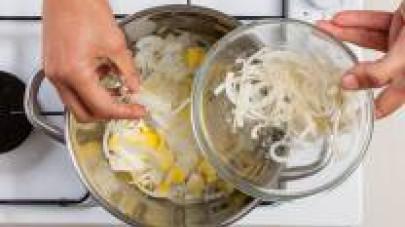 Infarinate le cipolle in 3 cucchiai di maizena e rosolatele in pentola con 2 cucchiai di olio extravergine di oliva, insieme alle patate,