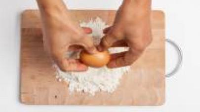 Preparate l'impasto per la pasta fresca: sulla spianatoia, formate una fontanella con la farina al centro, mettete le uova, un pizzico di sale e lavorate energeticamente sino ad ottenere un impasto om