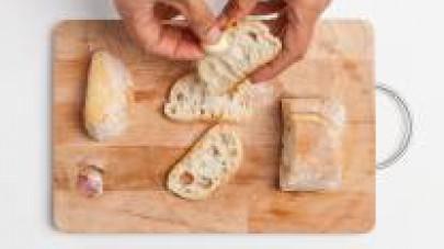 In una padella, rosolate le fettine di pane e strofinatele con 1 spicchio d'aglio. Quindi, farcitele con il patè