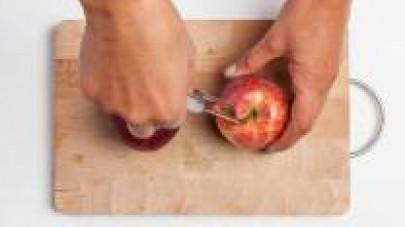 Lavate le mele bio, eliminate il torsolo e con lo stesso attrezzo praticate dei fori sulla superficie dei frutti. Riducete una parte del cioccolato fondente (100 g circa) a tocchetti.