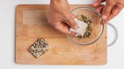 Mettete i semi tostati in una ciotola e impanate i filetti di merluzzo, premendo bene in modo che i semi aderiscano bene alla superficie del pesce