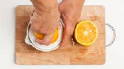 Spremete il succo d'arancia e tagliate finemente la buccia dell'agrume. Schiacciate lo spicchio d'aglio, dopo averlo privato dell'anima.
