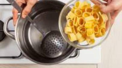 n una pentola capiente, cuocete la pasta in abbondante acqua salata. Scolatela dopo pochi minuti, perché deve essere condita ancora a dente.