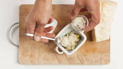 Adagiate alcune zucchine grigliate in una pirofila leggermente unta e coprite con il parmigiano