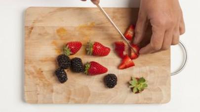 Lavate e mondate la frutta; tagliatela a cubetti.