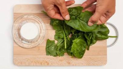 Pulite gli spinaci e lavateli sotto l'acqua corrente.