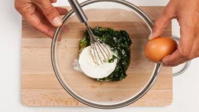 In una ciotola, disponete gli spinaci passati in padella, versate la ricotta e le uova.