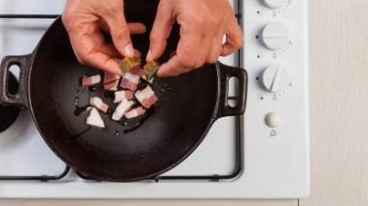 In un wok, rosolate il guanciale con l'olio extravergine di oliva. Aggiungete il dado Il Mio Duo Star - Sugo e poi le cipolline.