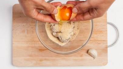 In una ciotola, mescolate la carne di manzo tritata con il pan grattato, l'uovo e l'aglio ben tritato, un pizzico di sale e di pepe.