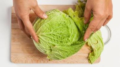 Lavate il cavolo verza, dopo aver eliminato le foglie esterne; quindi, tagliatelo a striscioline. Schiacciate l'aglio e pelate le patate.