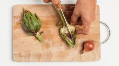 Pulite i carciofi, badando ad eliminare le foglie esterne e la barba interna.