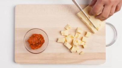 Fate cuocere la pasta in abbondante acqua salata e scolatela quando è ancora  al dente. Intanto tagliare il formaggio a tocchetti.