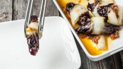 Adagiate le foglie di radicchio su un tagliere, farcitele con il manzo al ragù  arrotolate e servite.