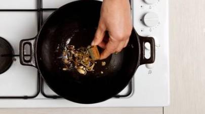 Quindi, aggiungete il riso e proseguite la cottura mescolando di frequente. Aggiungete acqua tiepida ogni volta che il liquido di cottura del riso si restringe eccessivamente.