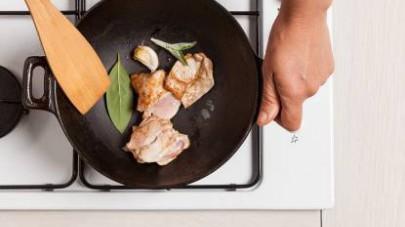 Nel frattempo, rosolate il pollo in un wok con lo spicchio di aglio in camicia, l'olio extravergine di oliva e 1 ciuffetto di salvia fresca.
