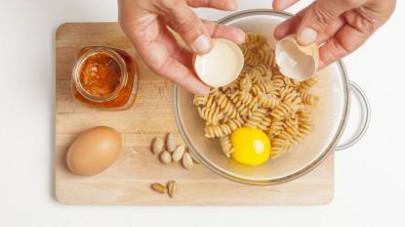 Versateli in una ciotola, unite le uova e condite con il GranPesto Tigullio Pomodori Secchi e Pistacchi.