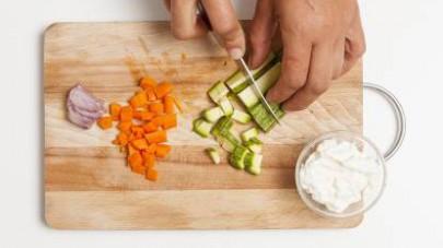 Affettate sottilmente lo scalogno, poi tagliate a cubetti le carote e le zucchine.