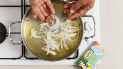 Mettete le cipolle a rosolare nell'olio extravergine di oliva caldo insieme al ½  cubetto di Il Mio Dado Star - Classico -30% di sale e fate cuocere mescolando fino a quando non saranno morbide.