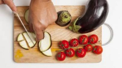 Lavate le verdure, asciugatele e tagliate a spicchi i pomodorini e a cubetti le melanzane.