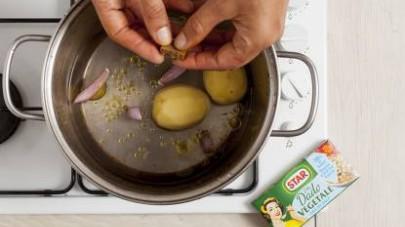 Pulite le ortiche (facendo attenzione a non pungervi), asciugatele e mettetele da parte. Pelate le patate e lo scalogno tagliando quest'ultimo a fettine e mettete entrambi a cuocere in una pentola dai