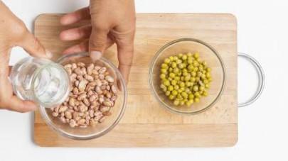 Risciacquate i fagioli borlotti sotto l'acqua corrente, poi metteteli in ammollo in una ciotola capiente per almeno 4 ore prima di scolarli.