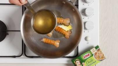 Lavate gli scampi sotto l'acqua corrente e privateli della testa, poi fateli cuocere in padella per qualche minuto bagnandoli con il brodo che avrete preparato con il Mio Dado Star - Vegetale con 9 ve