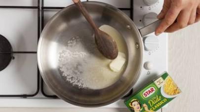 In un tegame fate sciogliere a fuoco dolce il burro, poi unite il riso e procedete con la tostatura, mescolando con un cucchiaio di legno per alcuni minuti fino a quando i chicchi non saranno lucidi e